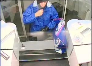 Das Bild zeigt den Täter mit auffällig blauer Jacke am Bankschalter. (Kapo TG)